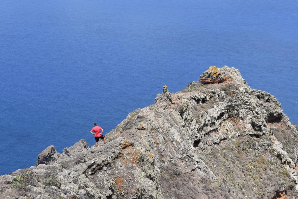 Skalní hřeben u moře, turista v červeném se rozhlíží