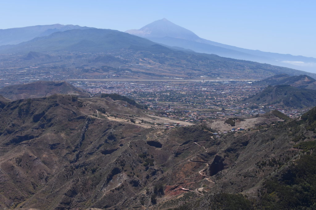 krajina s městem, klikatící se silnice, na horizontu výrazná hora