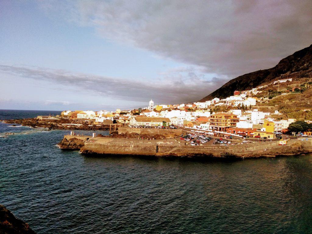 Městečko na břehu moře na úpatí kopce, bílé domy, zlatá hodina