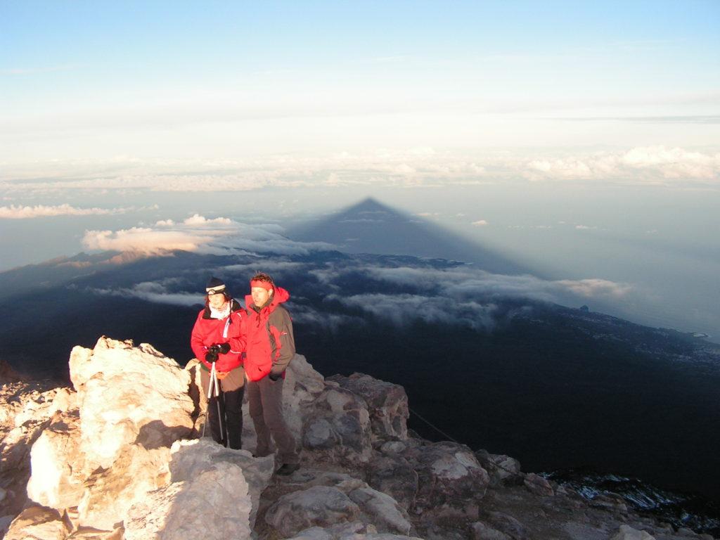 Dva turisté na vrcholku Pico del Teide, dlouhý stín přes moře